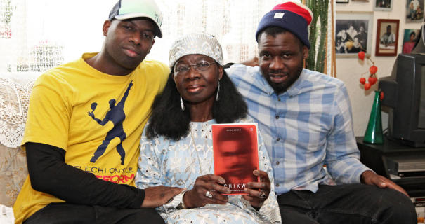 "Mrs Onyele, pictured with her sons Kelechi and Chima, holding a copy of her book Chikwe: Es bleibt ein Traum. The novel, written in German and whose title roughly translates as ""A Forlorn Dream"", chronicles the life of the eponymous Chikwe from a rural community in southeastern Nigeria to the German city of Frankfurt │© Menzel/Amani Verlag"