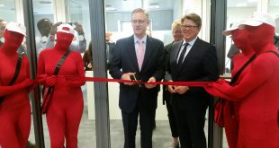 Alex Holmes, global CEO of MoneyGram, cuts the ribbon to open the new Germany's head office of the company while Michael Schütze, Vice President Central, Northern and Emerging Europe, Baltics at MoneyGram, looks on. Behind them is Irmgard Breucker, Marketing Director Central, Northern and Emerging Europe, Baltics │© Eromosele Jacob-Obinyan/TAC