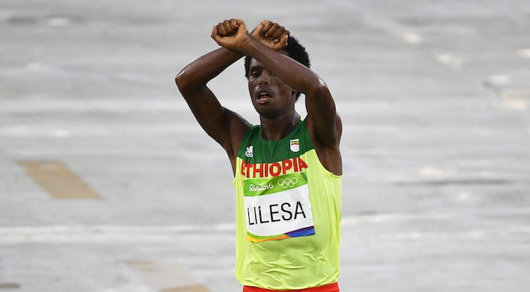 Feyisa Lilesa of Ethiopia makes the historic sign while crossing the finish line to take the second place in men's marathon. His action has brought the ethnic conflict in Ethiopia to global attention / © ANP/EPA/Franck Robichon