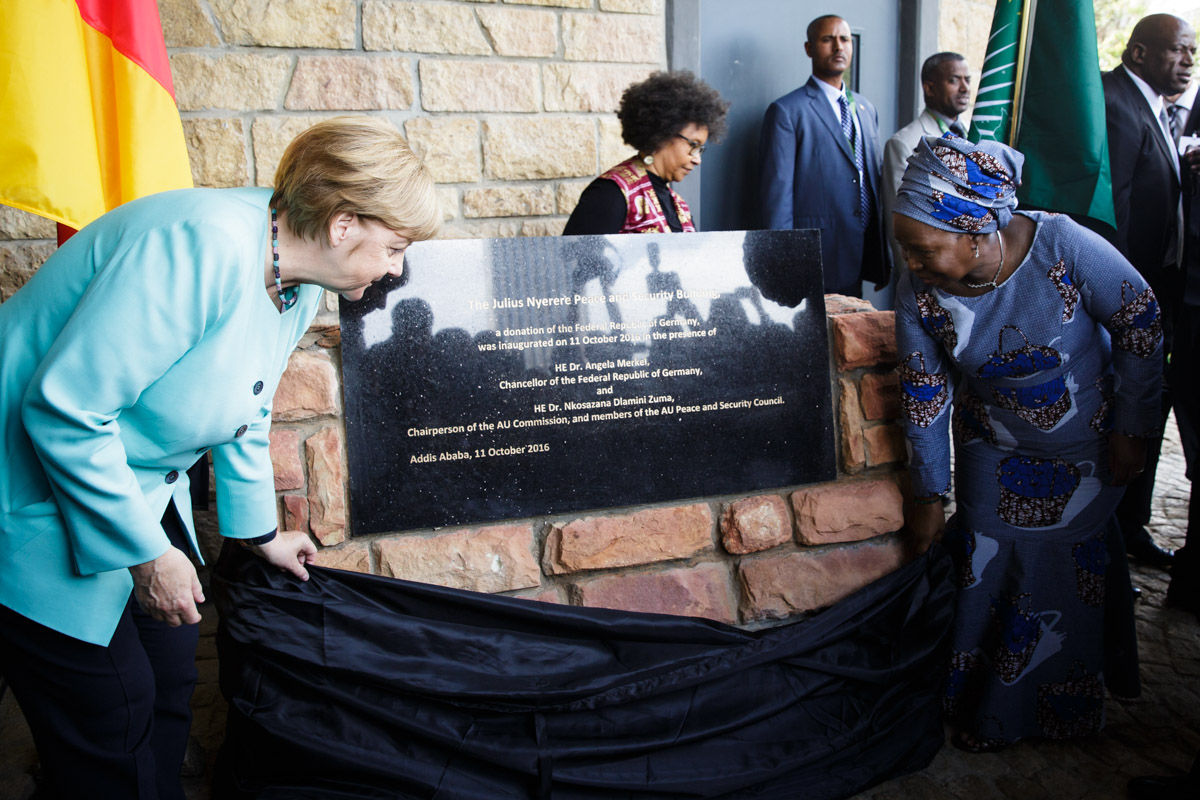 Chancellor Merkel (left) and African Union Commission chairperson, Dr Nkosazana Dlamini Zuma (right), unveil the plaque of the new Julius-Nyerere-Building for Peace and Security at the AU headquarters in Addis Ababa. The German government financed the construction of the building with a 30 million euro-grant as its contribution to promotion of stability in the continent / © Bundesregierung/Steins