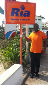 Ria's Operations Director for Africa, Robert Kotei, displays a newly installed Ria sign in Accra, Ghana│© Ria Money Transfer